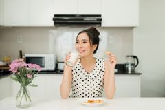 Young asian woman holding milk glass bite cookie in her kitchen.  Stock Photography