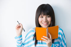 Young Asian woman holding notepad and pen Stock Photography