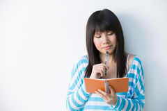 Young Asian woman holding notepad and pen Stock Images