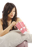 Young asian woman holding pillow eating popcorn Royalty Free Stock Photo