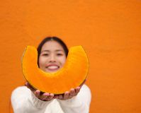 Young asian woman holding a slice of pumpkin Royalty Free Stock Photography