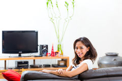 Young asian woman at home on the sofa Royalty Free Stock Image