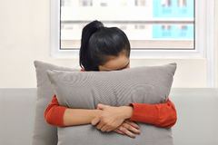 Young asian woman hugging and hiding behind a pillow Royalty Free Stock Photos