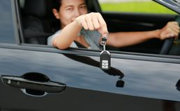Young asian woman inside a car, hold the key out from the window. Focus at a key hanging at her hand stock photos