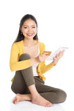 Young Asian woman internet shopping. Full length portrait of casual Asian woman sitting on floor using touch screen tablet pc for online shopping and making Royalty Free Stock Images