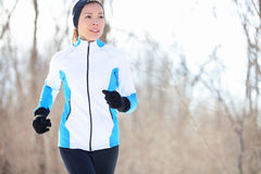 Young Asian woman jogging. Running young Asian woman jogging in a winter fleece and gloves in open countryside with copyspace in a health and fitness concept royalty free stock photography