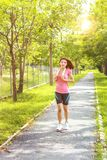 Young asian woman jogging during Outdoor Workout in a Park. Young asian woman. Female Runner Jogging during Outdoor Workout in a Park Royalty Free Stock Photo