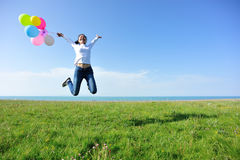 Young asian woman jumping with colored balloons Stock Image