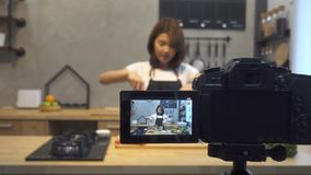 Young asian woman in kitchen recording video on camera. Smiling asian woman working on food blogger concept.