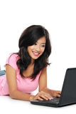 Young asian woman  with a laptop , laying on the floor isolated Royalty Free Stock Photography
