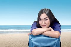 Young asian woman lean back on suitcase relaxing. On the beach Stock Image