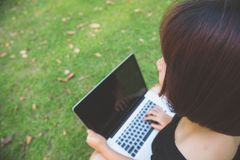 Young asian woman legs on the green grass with open laptop. Girl hands on keyboard. Distance learning concept. stock photography