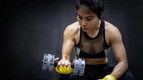 Asian woman lifting dumbbell in fitness gym stock images