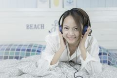 Young asian woman listening music in headphones on her bed. royalty free stock photography