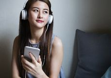 Young asian woman listening music. Royalty Free Stock Image