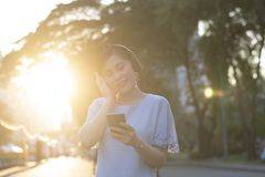Young Asian woman is listening to music by wearing wireless headphone and taking smartphone royalty free stock photography