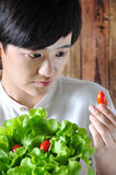 Young Asian Woman Looking at Selected Tomato Royalty Free Stock Photo
