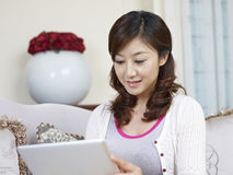 Young asian woman. Looking at tablet computer Stock Images
