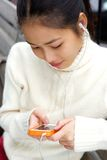 Young asian woman looking at text message on mobile phone Stock Image