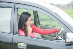 Young Asian woman looks stress while driving her car Royalty Free Stock Photos