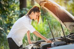 Young asian woman looks under the hood of a broken car. Thailand Royalty Free Stock Photography