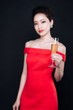 Young asian woman in luxury red dress with glass of sparkling wi. Ne. Party, drinks, holidays and celebration concept stock image