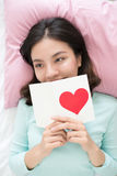 Young asian woman lying on bed, holding greeting card with red h. Eart shape Royalty Free Stock Photos