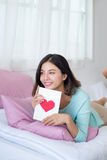 Young asian woman lying on bed, holding greeting card with red h. Eart shape Stock Photos