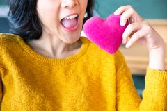 Young asian woman making air bite to the pink pillow. royalty free stock photo