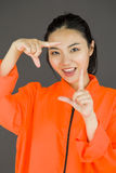 Young Asian woman making frame with fingers in prisoners uniform Stock Images