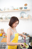 Young asian woman making salad in kitchen smiling and laughing h. Appy at home Stock Photos