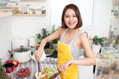 Young asian woman making salad in kitchen smiling and laughing h. Appy at home Stock Images