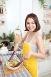 Young asian woman making salad in kitchen smiling and laughing h. Appy at home Royalty Free Stock Photos