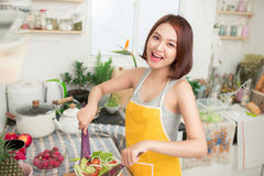 Young asian woman making salad in kitchen smiling and laughing h. Appy at home Royalty Free Stock Photo