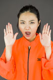 Young Asian woman making stop gesture sign from both hands in prisoners uniform Royalty Free Stock Photography