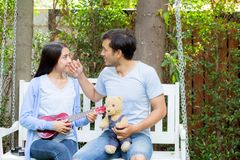 Young asian woman and man couple sitting at park playing ukulele and sing a song Stock Photography