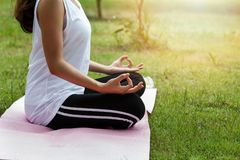 Young asian woman meditating while sitting in lotus pose on yoga mat Stock Photography