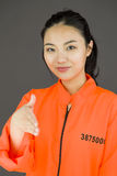 Young Asian woman offering hand for handshake in prisoners uniform Stock Photo