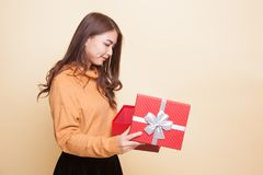 Young Asian woman open a gift box. Young Asian woman open a gift box on beige background Royalty Free Stock Image