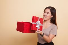 Young Asian woman open a gift box. Young Asian woman open a gift box on beige background Stock Image
