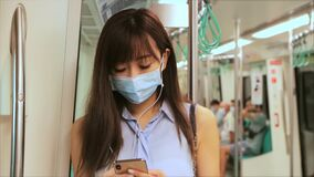 Young Asian woman passenger wearing surgical mask and listening music via mobile phone in subway train