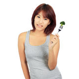 Young asian woman with a picec of brocolli Royalty Free Stock Photo