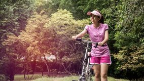Young asian woman in pink sportswear and folding bike during recreation time in the park. Beautiful sunny day.  stock photography