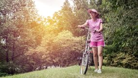 Young asian woman in pink sportswear and folding bike during recreation time in the park. Beautiful sunny day.  royalty free stock images