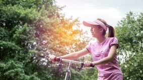 Young asian woman in pink sportswear and folding bike during recreation time in the park. Beautiful sunny day.  royalty free stock photos
