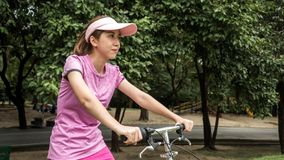 Young asian woman in pink sportswear and folding bike during recreation time in the park. Beautiful sunny day.  royalty free stock image