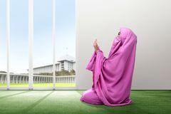 Young asian woman in pink veil sit in praying position on the carpet inside the room stock photos