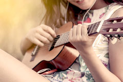 Young asian woman playing acoustic guitalele Royalty Free Stock Photos