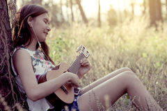 Young asian woman playing acoustic guitalele Royalty Free Stock Images
