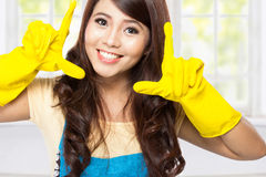 Young asian woman playing around with a yellow latex gloves on Royalty Free Stock Photography